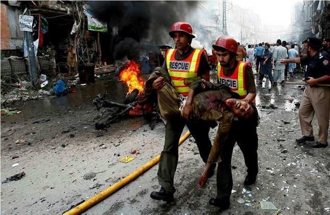 ATTENTION EDITORS - VISUAL COVERAGE OF SCENES OF INJURY OR DEATH Rescue workers move a body from the site of a bomb attack in Peshawar September 29, 2013. Twin blasts in the northwestern Pakistan city of Peshawar killed 33 people and wounded 70 on Sunday, a week after two bombings at a church in the frontier city killed scores, police and hospital authorities said.REUTERS/Khuram Parvez    (PAKISTAN - Tags: POLITICS CIVIL UNREST CRIME LAW)  TEMPLATE OUT